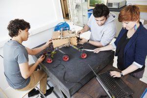3 étudiants fabriquant un robot hexapode