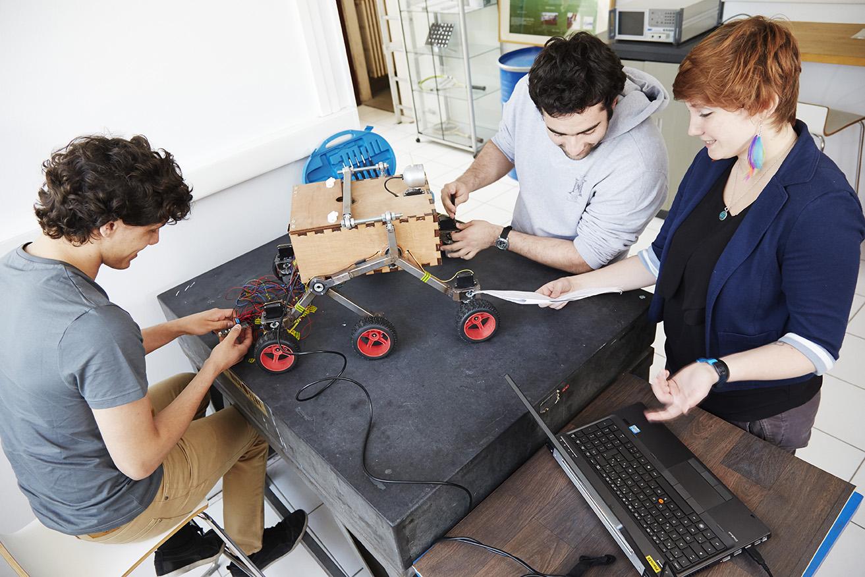 Trois étudiants de Supméca travaillent sur un robot mécanique à six roues