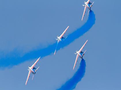 4 avions survolant le ciel avec une trainée de fumée bleue
