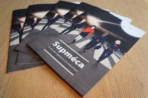nouvelle brochures Supméca posées en éventail sur une table, la couverture représente 4 étudiants marchant sur un tarmac de nuit