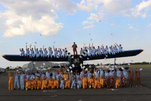Les candidats du Hop ! Tour des jeunes pilotes posent devant un avion avant le début de cette expérience, accompagnés de leurs instructeurs de vol.