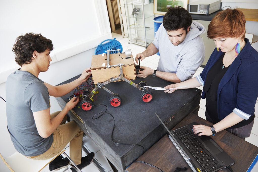 3 étudiants travaillent sur un prototype de robot à 6 roues