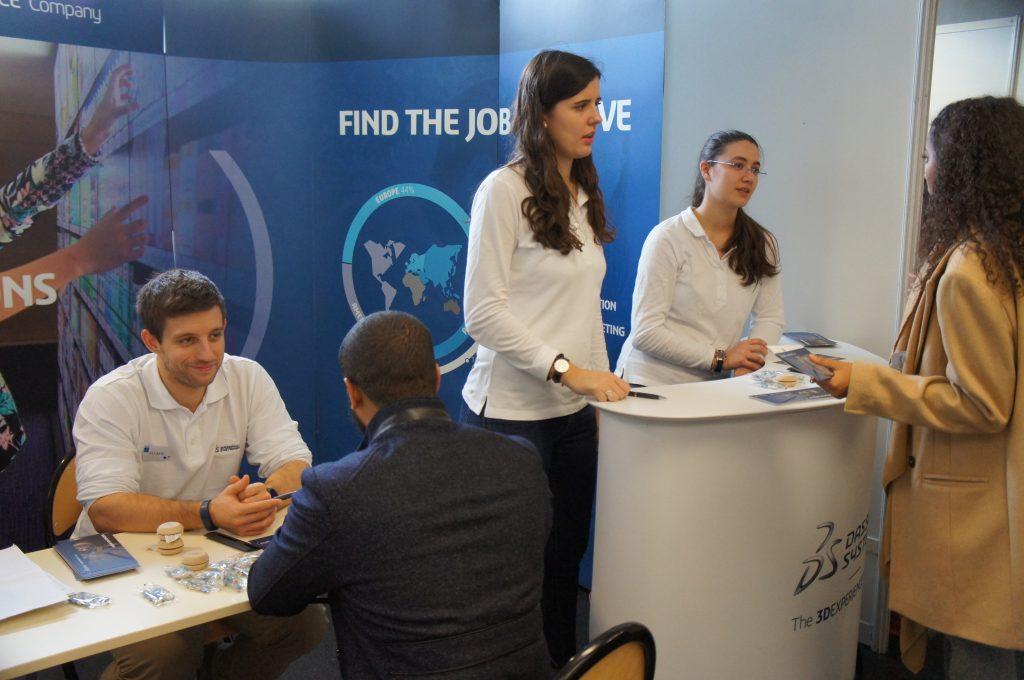 Photo d'un stand au forum entreprise ENSEA Supméca, des professionnels hommes et femmes font face à des étudiants