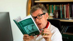 L'acteur David Lowe tient un livre sur le thème des vibrations dans une main et lâche un grand ressort de l'autre