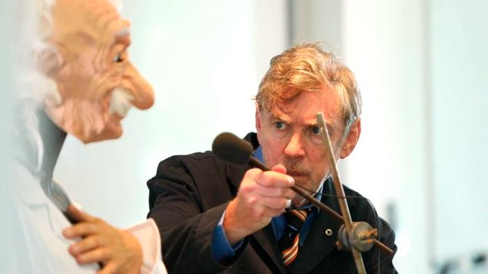 L'acteur David Lowe règle un micro devant un manequin avec un masque d'Einstein