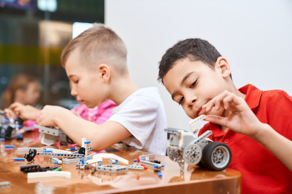 Deux enfants jouent et fabriquent des voitures.